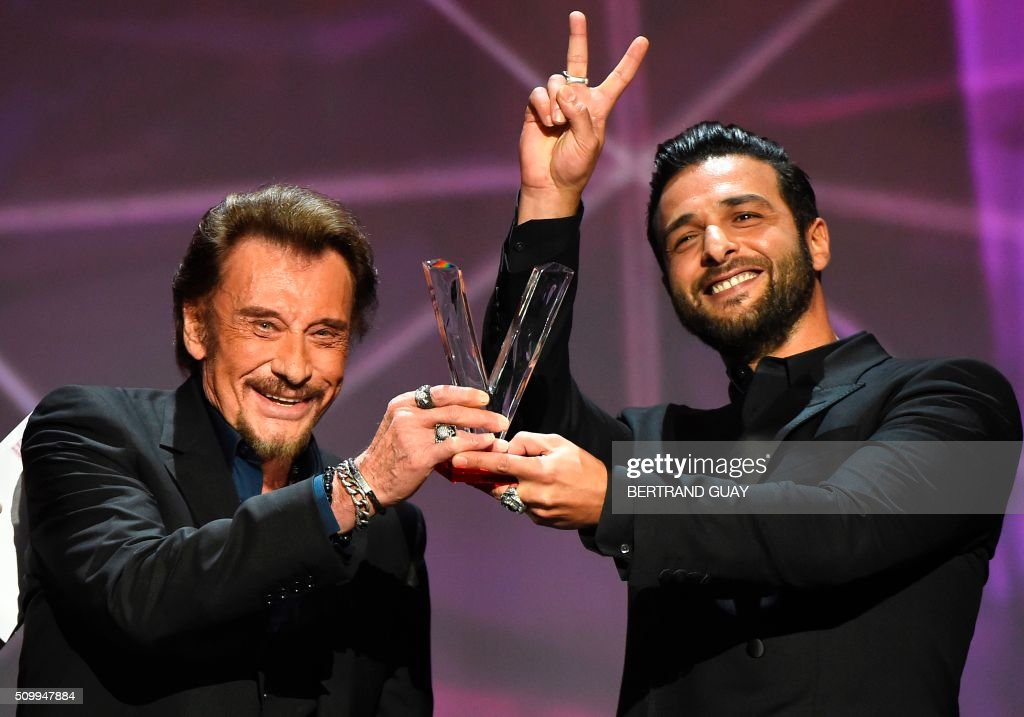 French singer Johnny Hallyday (L) smiles as he receives the best album award composed by Maxim Nucci alias Yodelice (R), during the 31st Victoires de la Musique, the annual French music awards ceremony, on February 12, 2016 at the Zenith concert hall in Paris. / AFP / BERTRAND GUAY