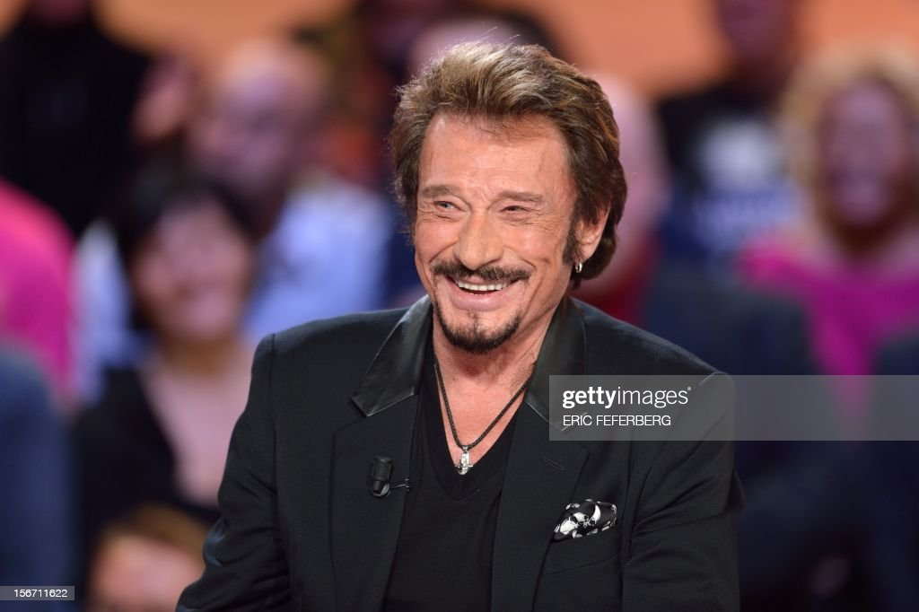French singer Johnny Hallyday smiles as he takes part in the TV show 'Le grand journal' on a set of French TV Canal+, on November 19, 2012 in Paris, to present his new album entitled, 'The wait'.