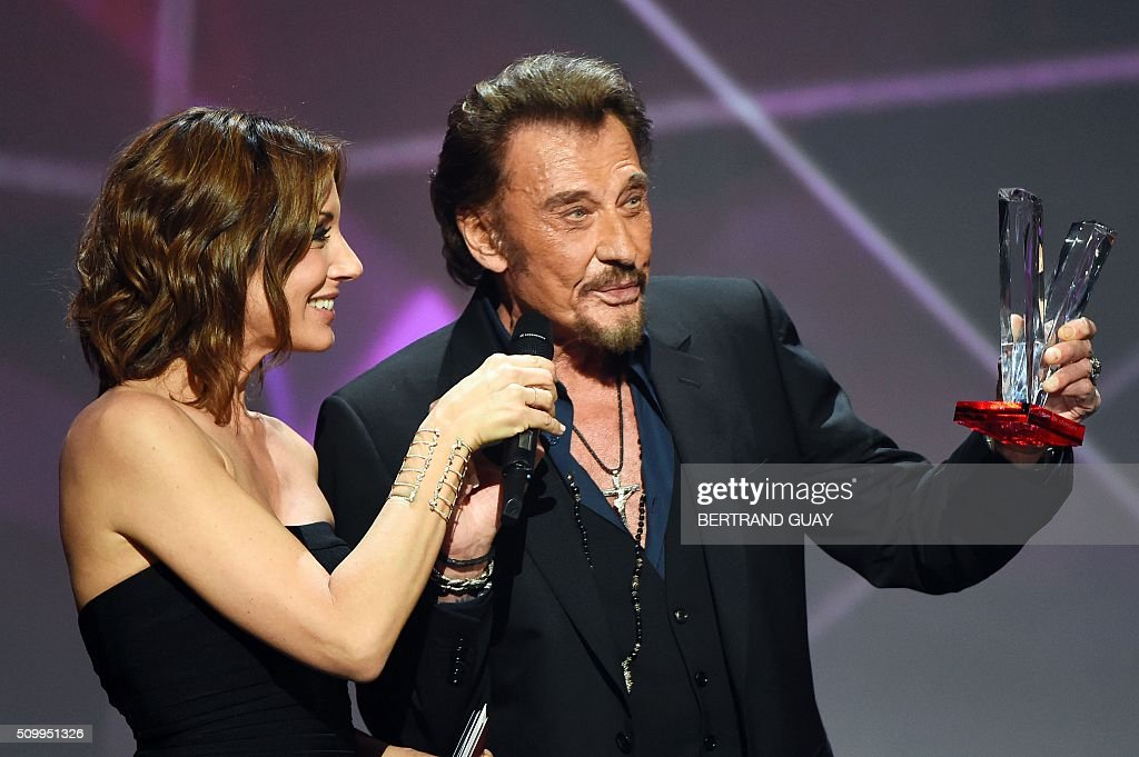 French singer Johnny Hallyday (R) speaks as he holds the best album award next to French TV host Virginie Guilhaume on stage during the 31st Victoires de la Musique, the annual French music awards ceremony, on February 12, 2016 at the Zenith concert hall in Paris. / AFP / BERTRAND GUAY