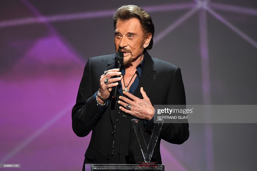 French singer Johnny Hallyday speaks as he receives the best album award on stage during the 31st Victoires de la Musique, the annual French music awards ceremony, on February 12, 2016 at the Zenith concert hall in Paris. / AFP / BERTRAND GUAY