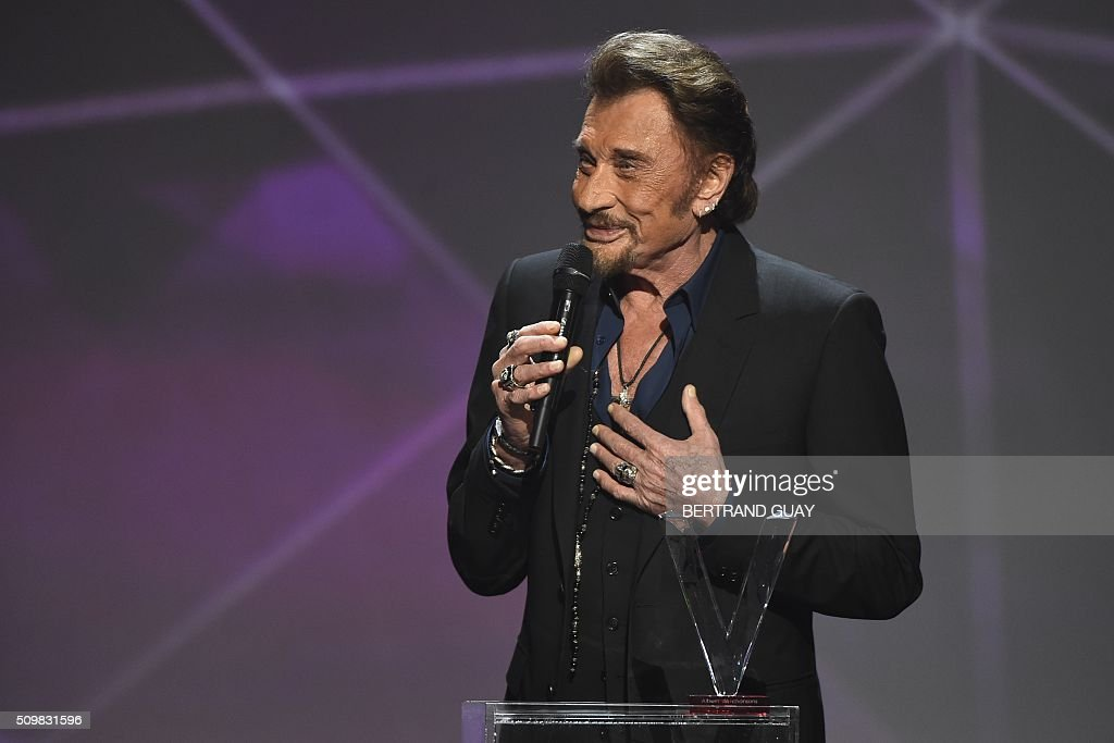 French singer Johnny Hallyday speaks as he receives the best chanson album award during the 31st Victoires de la Musique, the annual French music awards ceremony, on February 12, 2016 at the Zenith concert hall in Paris. AFP PHOTO / BERTRAND GUAY / AFP / BERTRAND GUAY