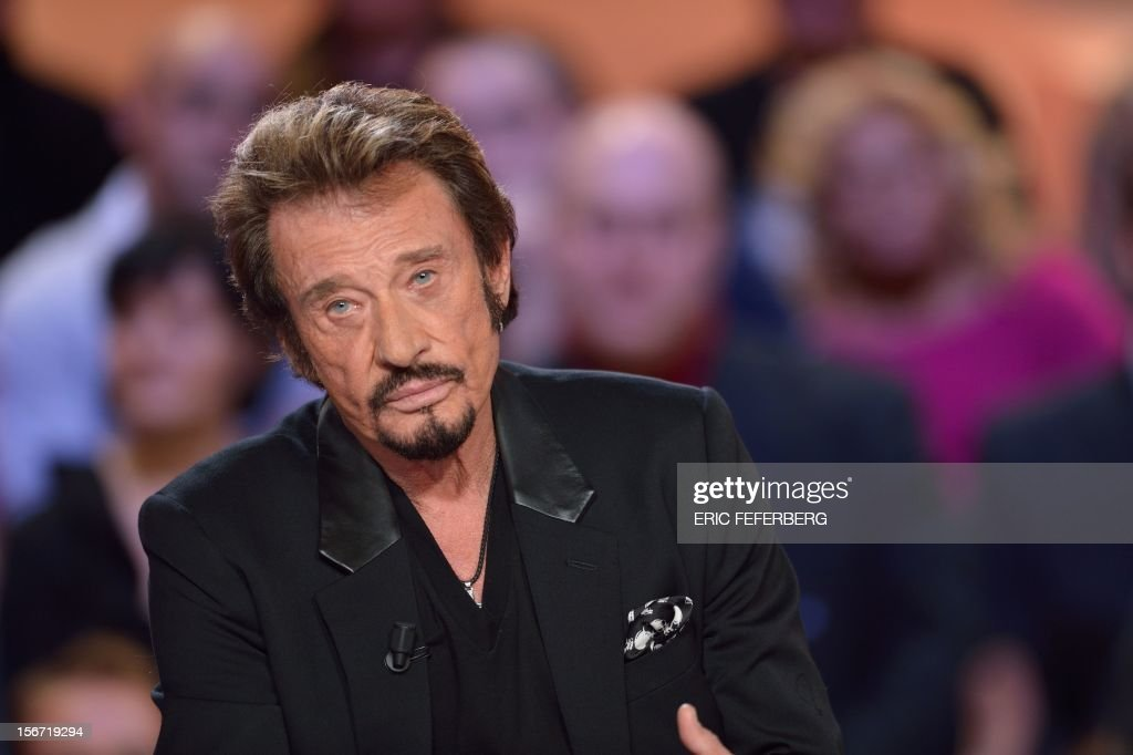 French singer Johnny Hallyday speaks as he takes part in the TV show 'Le grand journal' on a set of French TV Canal+, on November 19, 2012 in Paris, to present his new album entitled, 'The wait'. AFP PHOTO/ERIC FEFERBERG