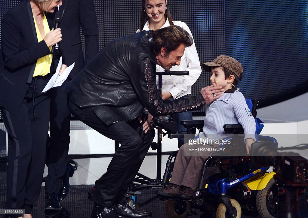 French singer Johnny Hallyday (C) speaks with a child, Thibault, during the 26th Telethon, France's biggest annual fund-raising event during 30 hours of live television transmission, on December 7, 2012 in Saint-Denis, north of Paris. The event, aiming at collecting funds for research on genetic diseases such as myopathy, a neuromuscular disease, will take place on December 7 and 8, 2012.