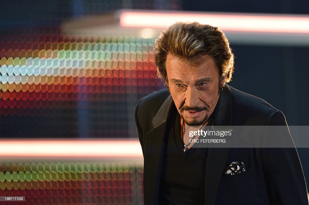 French singer Johnny Hallyday stands to sing a song of his new album entitled, 'The wait', as he takes part in the TV show 'Le grand journal' on a set of French TV Canal+, on November 19, 2012 in Paris.