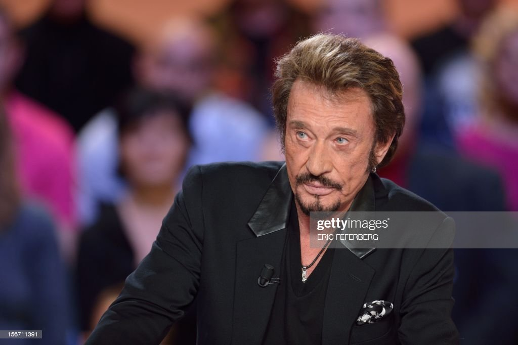 French singer Johnny Hallyday takes part in the TV show 'Le grand journal' on a set of French TV Canal+, on November 19, 2012 in Paris, to present his new album entitled, 'The wait'. AFP PHOTO/ERIC FEFERBERG