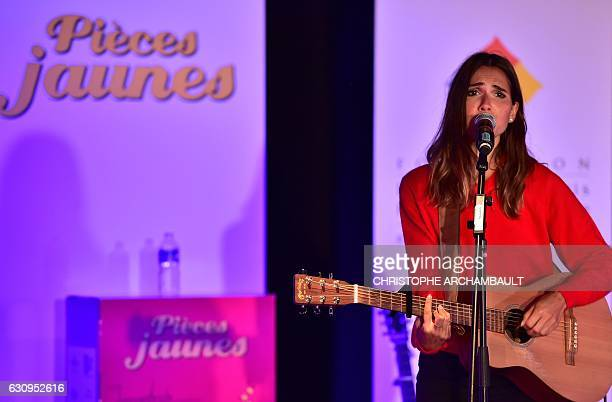 French singer Joyce Jonathan sings for children during the launch of the 28th edition of the 'Pieces Jaunes' collection operation at the Necker...