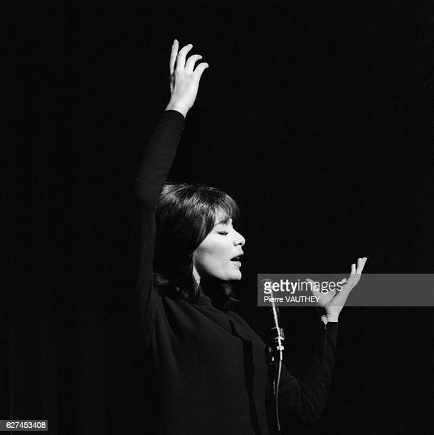 French singer Juliette Greco raises her arms during her performance at the Olympia Concert Hall in Paris