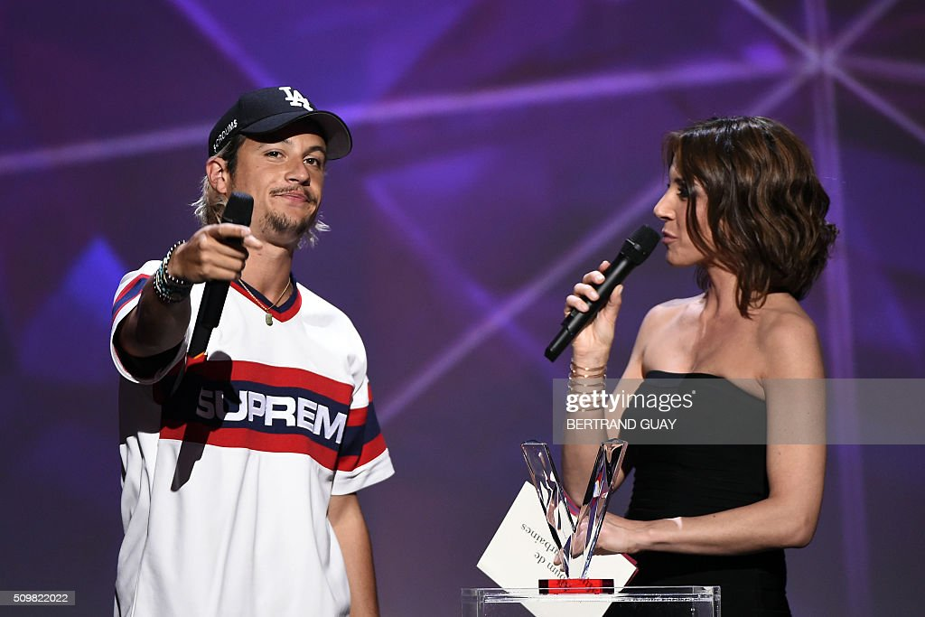French singer Ken Samaras aka Nekfeu (L), flanked by French TV host and Master of Ceremony Virginie Guilhaume (R), receives the best urban music album award during the 31st Victoires de la Musique, the annual French music awards ceremony, on February 12, 2016 at the Zenith concert hall in Paris. AFP PHOTO / BERTRAND GUAY / AFP / BERTRAND GUAY