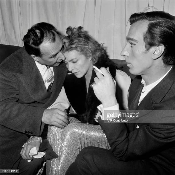 French singer Line Renaud is comforted by her husband Loulou Gasté and dancer Fernando Rego after the fire occured on the stage of the Casino de...