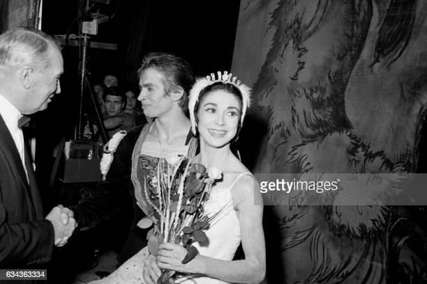 French singer Maurice Chevalier congratulates British dancer Margot Fonteyn and Soviet ballet dancer Rudolf Noureev after the show of 'Le lac des...
