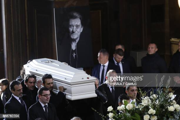 French singer Maxim Nucci aka Yodelice manager Sebastien Farran along with relatives of late French singer Johnny Hallyday carry the coffin as they...