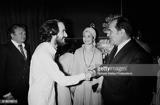 French singer Michel Fugain shakes hands with French politician Francois Mitterrand and actress MarieJose Nat backstage after a concert at the...