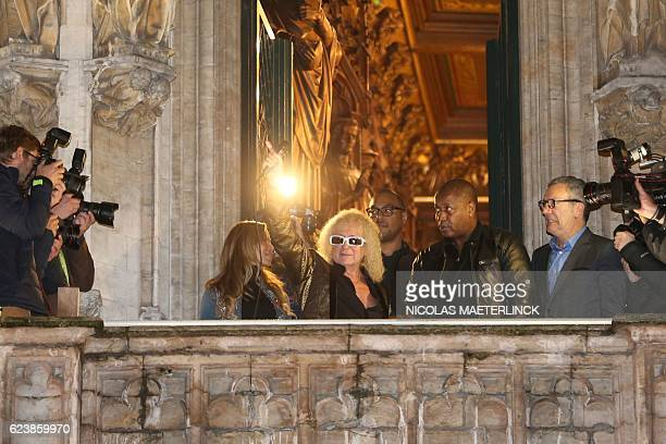 French singer Michel Polnareff flanked by his wife Danyellah Polnareff gestures from the balcony of the city hall in Brussels on November 17 as the...