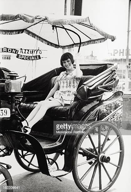 French singer Mireille Mathieu poses smiling sitting on a cart Neaple 1972