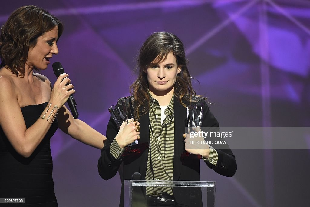 French singer of the band 'Christine and the Queens' Heloise Letissier (R), flanked by French TV host and Master of Ceremony Virginie Guilhaume (L), smiles as she received the best newcomer live show award and the best video clip award during the 31st Victoires de la Musique, the annual French music awards ceremony, on February 12, 2016 at the Zenith concert hall in Paris. AFP PHOTO / BERTRAND GUAY / AFP / BERTRAND GUAY