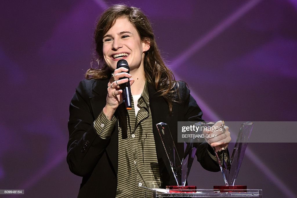 French singer of the band 'Christine and the Queens' Heloise Letissier smiles as she received the best live show award and the best video clip award during the 31st Victoires de la Musique, the annual French music awards ceremony, on February 12, 2016 at the Zenith concert hall in Paris. / AFP / BERTRAND GUAY
