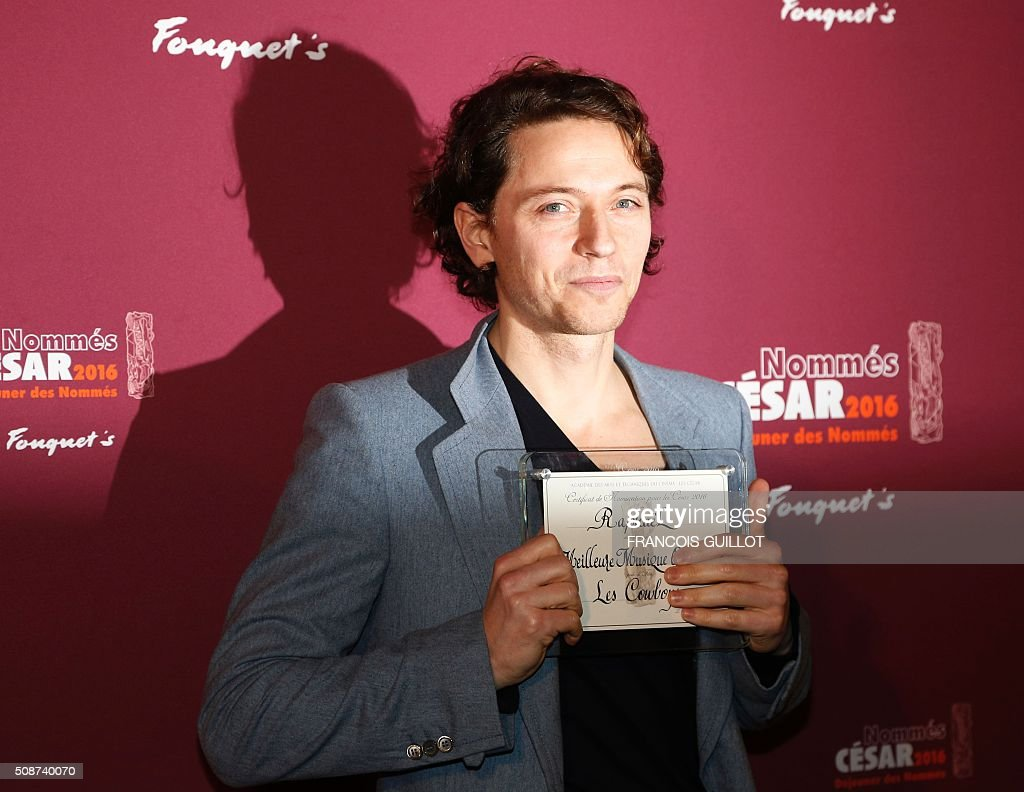 French singer Raphael poses with his nomination certificate for Best Original Music during the nominations event for the 2016 César film awards, on February 6, 2016 in Paris. The 41st Ceremony for the Cesar film award, considered as the highest film honour in France, will take place on February 26, 2016. / AFP / FRANCOIS GUILLOT