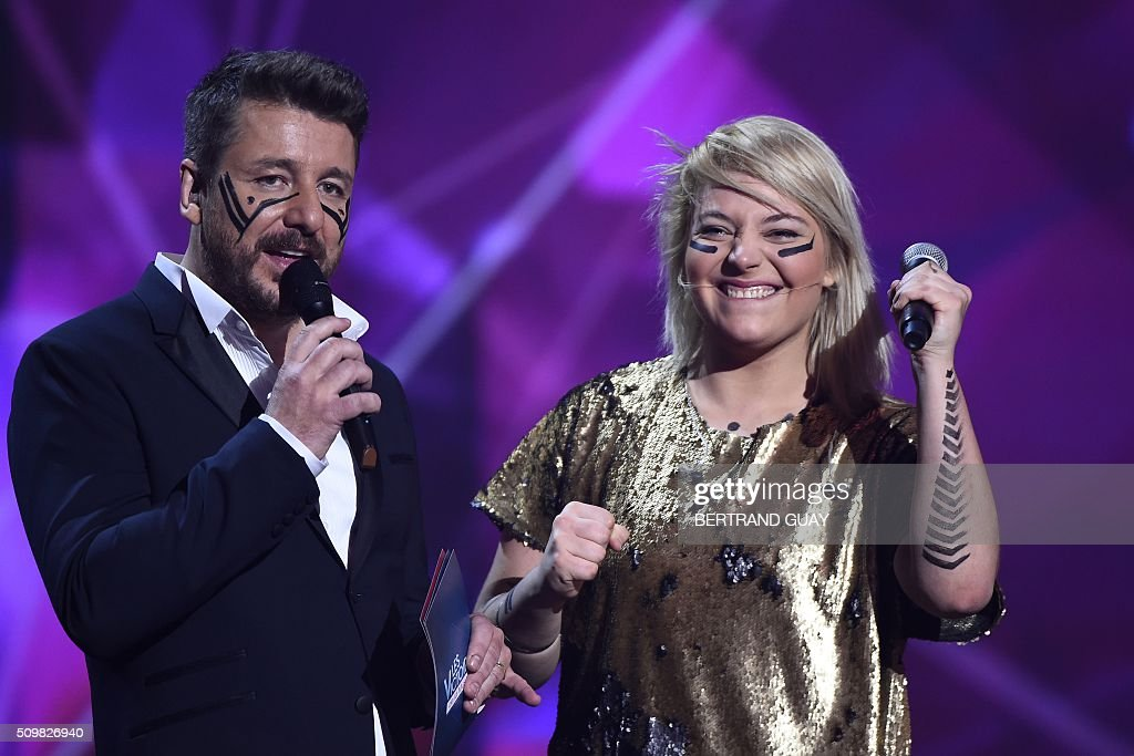 French singer Santa (R) of the French pop rock band Hyphen Hyphen smiles, flanked by French TV host and Master of Ceremony Bruno Guillon (L) during the 31st Victoires de la Musique, the annual French music awards ceremony, on February 12, 2016 at the Zenith concert hall in Paris. AFP PHOTO / BERTRAND GUAY / AFP / BERTRAND GUAY