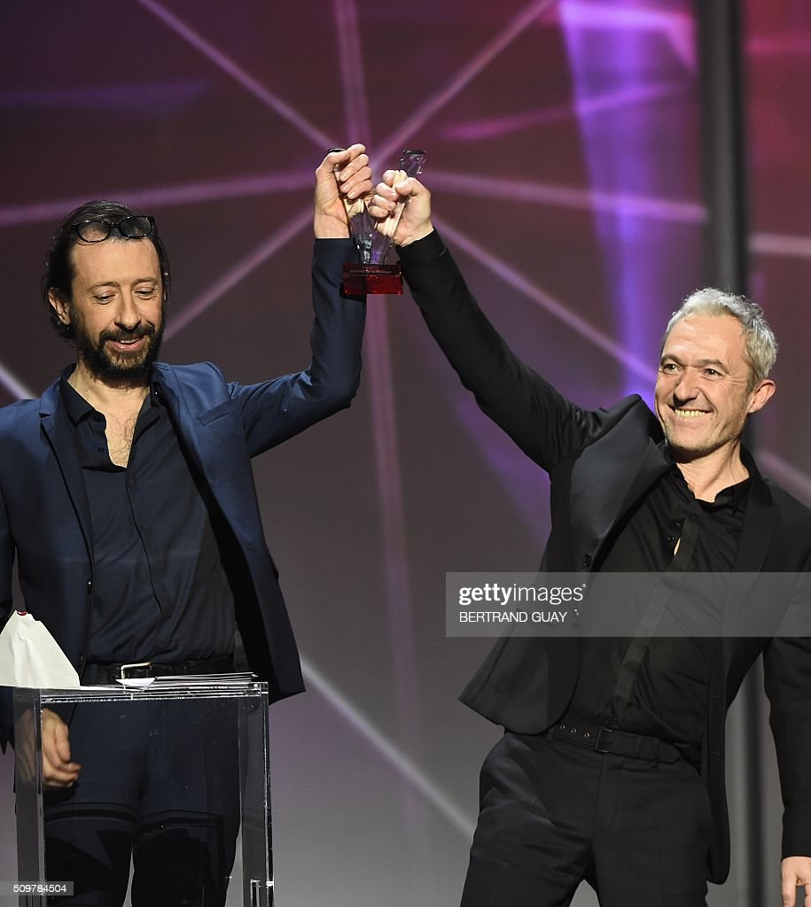 French singers and guitarists of the band 'Les Innocents' Jean-Philippe Nataf (L) and Jean-Christophe Urbain (R), pose after receiving the best rock album award, during the 31st Victoires de la Musique, the annual French music awards ceremony, on February 12, 2016 at the Zenith concert hall in Paris. AFP PHOTO / BERTRAND GUAY / AFP / BERTRAND GUAY