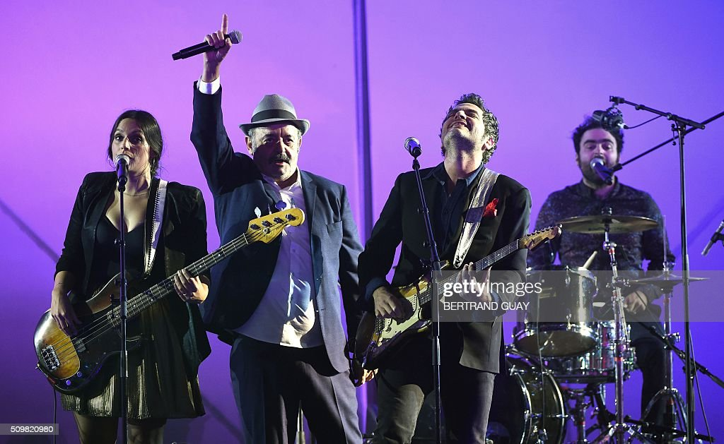 French singers and musicians (from L) Anna, Louis, Matthieu and Joseph Chedid perform on stage with French TV host and Master of Ceremony Virginie Guilhaume (L) during the 31st Victoires de la Musique, the annual French music awards ceremony, on February 12, 2016 at the Zenith concert hall in Paris. AFP PHOTO / BERTRAND GUAY / AFP / BERTRAND GUAY