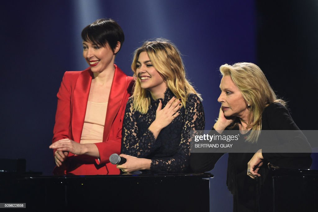 French singers Jeanne Cherhal, Louane and Veronique Sanson listen to French singer and composer William Sheller performing on stage during the 31st Victoires de la Musique, the annual French music awards ceremony, on February 12, 2016 at the Zenith concert hall in Paris. AFP PHOTO / BERTRAND GUAY / AFP / BERTRAND GUAY