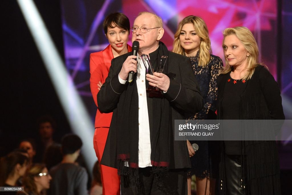French singers Jeanne Cherhal (L), Louane (2nd R) and Veronique Sanson (R) look at French singer and composer William Sheller (2nd L) speaking after receiving a special honour during the 31st Victoires de la Musique, the annual French music awards ceremony, on February 12, 2016 at the Zenith concert hall in Paris. AFP PHOTO / BERTRAND GUAY / AFP / BERTRAND GUAY