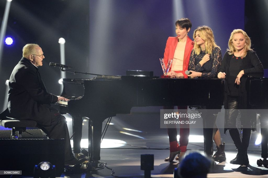 French singers Jeanne Cherhal (2nd L), Louane (C) and Veronique Sanson (R) look at French singer and composer William Sheller (L) performing during the 31st Victoires de la Musique, the annual French music awards ceremony, on February 12, 2016 at the Zenith concert hall in Paris. AFP PHOTO / BERTRAND GUAY / AFP / BERTRAND GUAY