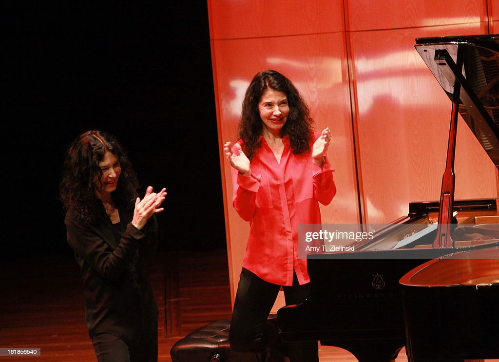 French sisters, concert pianists Katia Labeque (L) and Marielle Labeque applaude after a vocal performance by their percussionists Kalakan Trio after they performed together Ravel's 'Bolero' arrangement for duo piano as part of 'Imagine' family concerts programming at the Queen Elizabeth Hall on February 17, 2013 in London, England.