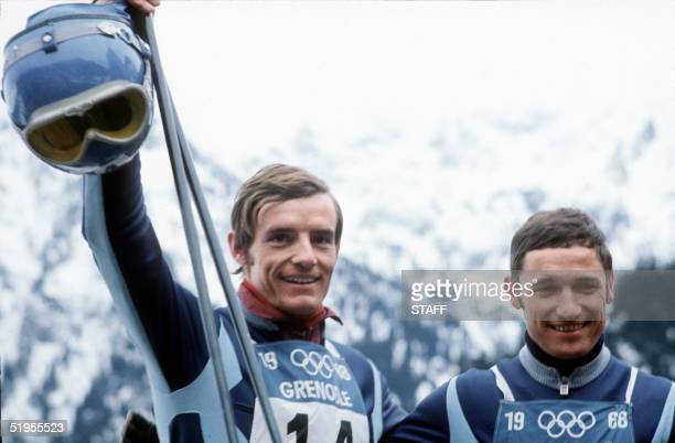 French skiers JeanClaude Killy standing next to compatriot Guy Perillat salutes the crowd 09 February 1968 in Chamrousse near Grenoble after winning...