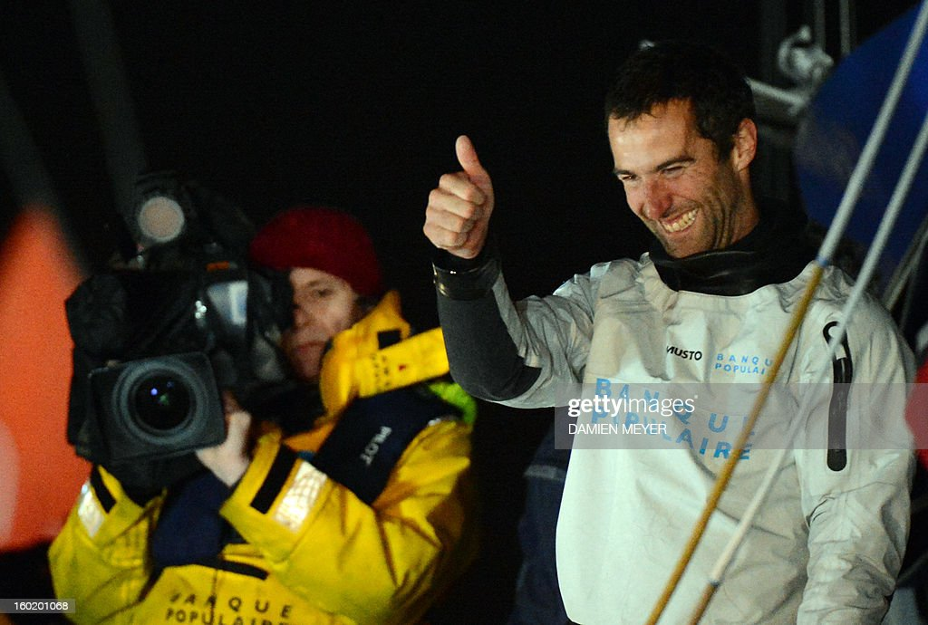 French skipper Armel Le Cleach gives a thumb up from his boat 'Banque Populaire' after crossing the finish line of the 7th edition of the Vendee Globe solo round-the-world race on January 27, 2013 off the coasts of Les Sables d'Olonne, western France. France's Francois Gabart, 29, set a new record with 78 days 02 h and 16 min, beating the previous record time set at 84 days 3hr 9min by 2009 winner Michel Desjoyeaux, and Le Cleach placed second.