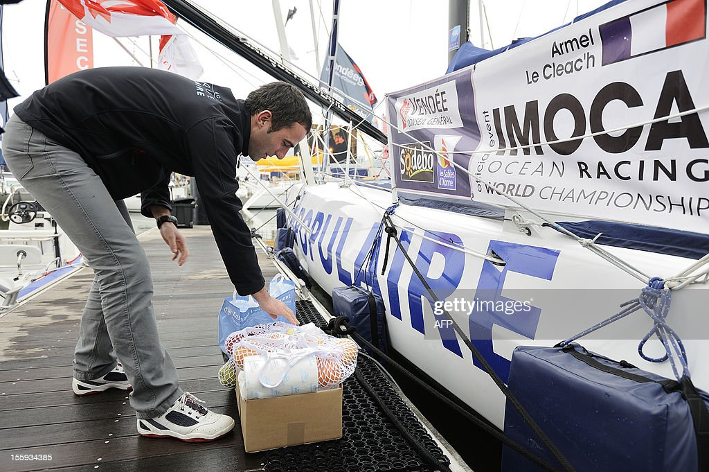 French skipper Armel Le Cleac'h packs fresh food by his monohull 'Banque Populaire'on November 9, 2012 in Les Sables d'Olonne, western France on the eve of the start of the 7th edition of the Vendee Globe solo round-the-world race. AFP PHOTO JEAN-SEBASTIEN EVRARD