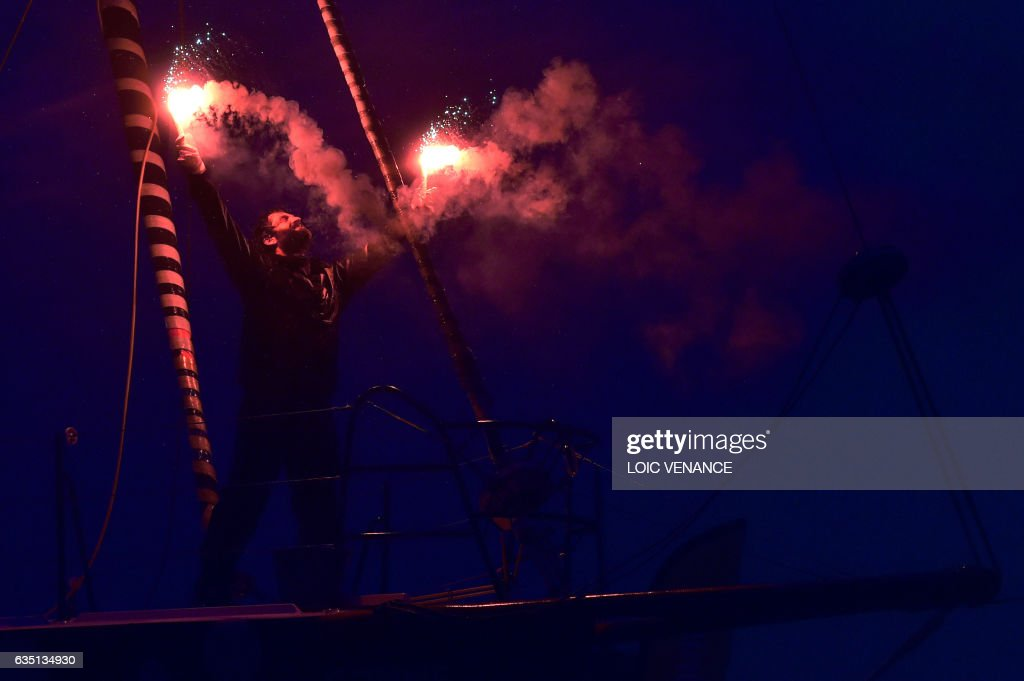 French skipper Eric Bellion celebrates aboard his Imoca 60 'Comme un seul Homme' as he arrives at Les Sables d'Olonne after placing 9th of the Vendee Globe solo around-the-world sailing race on February 13, 2017. /