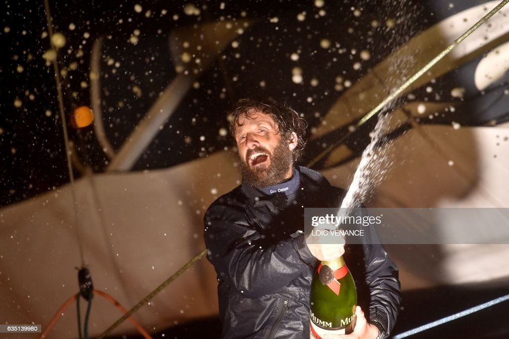 French skipper Eric Bellion (L) celebrates with Champagne aboard his Imoca 60 'Comme un seul Homme' as he arrives at Les Sables d'Olonne after placing 9th of the Vendee Globe solo around-the-world sailing race on February 13, 2017. /