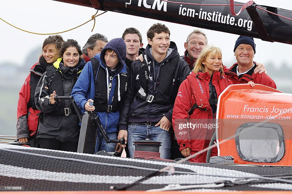 French skipper Francis Joyon (R) and his wife Virginie (2ndR) and his family pose on his multihull upon his arrival at Brest harbour on June 17, 2013, western France, after becoming the fastest man to cross the Atlantic Ocean single-handed on a multihull in 5 days, 2 hours, 56 minutes and 10 seconds, beating the previous record by French skipper Thomas Coville. AFP PHOTO / JEAN-SEBASTIEN EVRARD