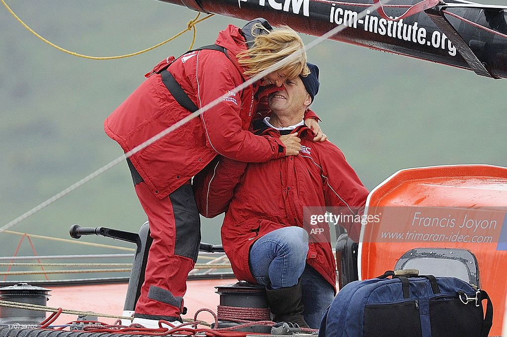 French skipper Francis Joyon celebrates with his wife Virginie on his multihull IDEC upon his arrival at Brest harbour on June 17, 2013, western France, after becoming the fastest man to cross the Atlantic Ocean single-handed on a multihull in 5 days, 2 hours, 56 minutes and 10 seconds, beating the previous record by French skipper Thomas Coville.