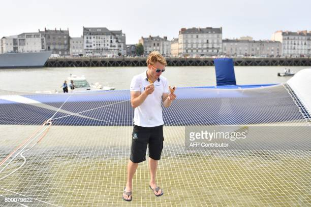 French skipper Francois Gabart eats an ice cream aboard his Macif Ultim multihull on June 22 2017 in Nantes western France prior to take part in the...