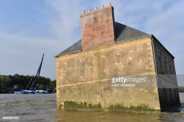 TOPSHOT French skipper Francois Gabart sails his Ultim multihull Macif past the house in the Loire River by artist JeanLuc Courcoult off Coueron on...