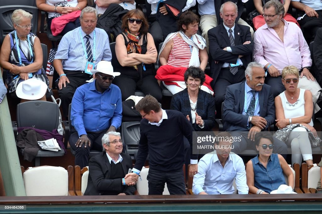 French skipper Isabelle Autissier (2nd row 2nd R), former tennis player Mansour Bahrami (2nd row R), look on as French actor Michel Boujenah (forst row, L) shakes hands with French Junior Minister for Development Pascal Canfin (C) next to former Argentinian rugby player Gonzalo Quesada (2nd R) attend the men's second round match between France's Jo-Wilfried Tsonga and Cyprus' Marcos Baghdatis at the Roland Garros 2016 French Tennis Open in Paris on May 26, 2016. / AFP / MARTIN