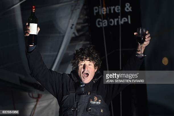 French skipper Jean Le Cam celebrates with a glass of red wine aboard his class Imoca monohull 'Finistere Mer Vent' after he finished 6th of the...