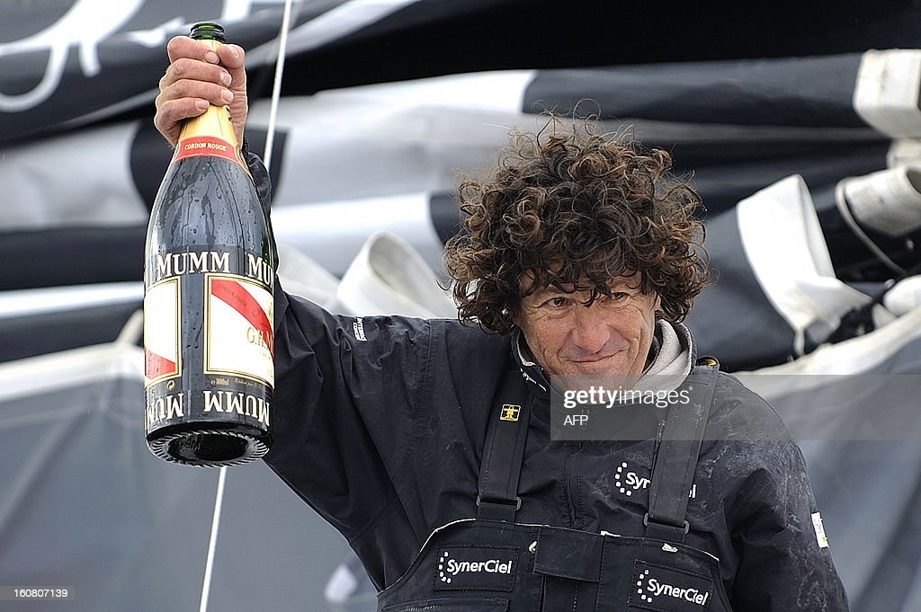 French skipper Jean Le Cam holds a bottle of Champagne as he celebrates on his monohull 'SynerCiel' upon his arrival at the 7th edition of the Vendee Globe solo round-the-world race on February 6, 2013 in Les Sables d'Olonne, western France. Le Cam finished in 5th position after 88 days at sea.
