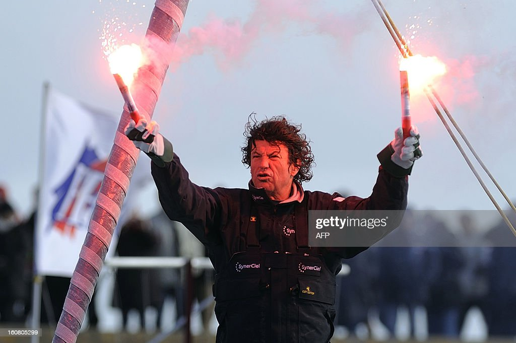 French skipper Jean Le Cam holds light flares as he celebrates on his monohull 'SynerCiel' upon his arrival at the 7th edition of the Vendee Globe solo round-the-world race on February 6, 2013 in Les Sables d'Olonne, western France. Le Cam finished in 5th position after 88 days at sea. AFP PHOTO / JEAN-SEBASTIEN EVRARD
