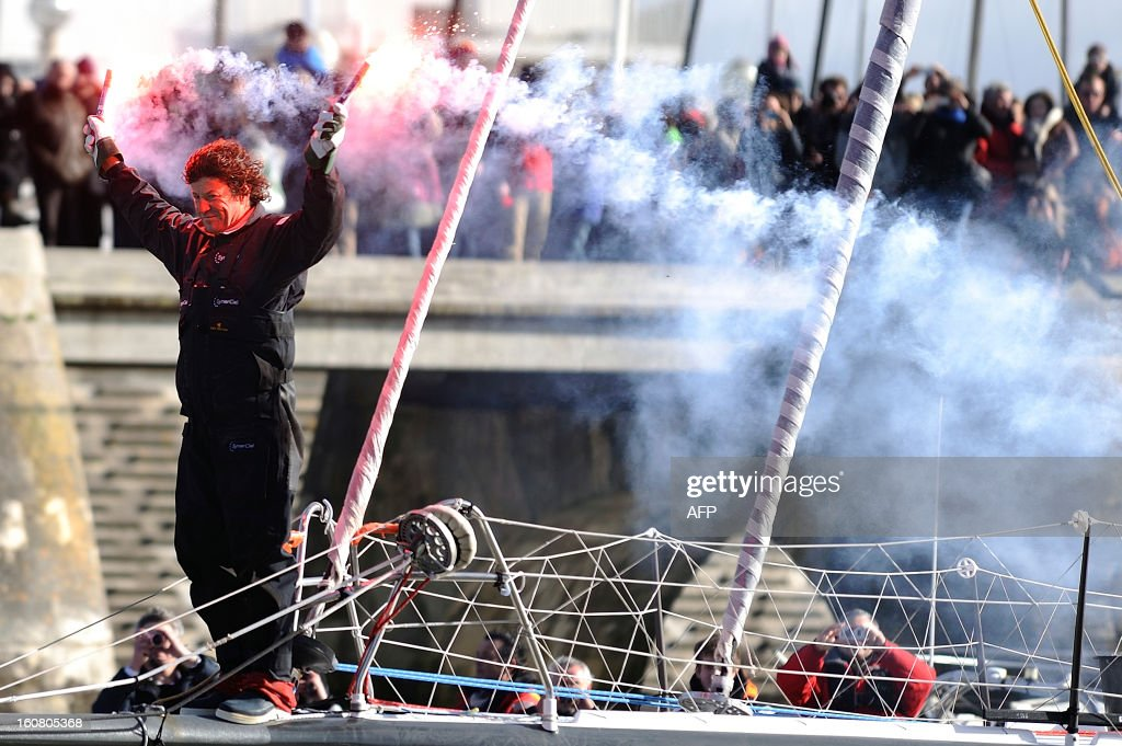 French skipper Jean Le Cam holds light flares as he celebrates on his monohull 'SynerCiel' upon his arrival at the 7th edition of the Vendee Globe solo round-the-world race on February 6, 2013 in Les Sables d'Olonne, western France. Le Cam finished in 5th position after 88 days at sea.