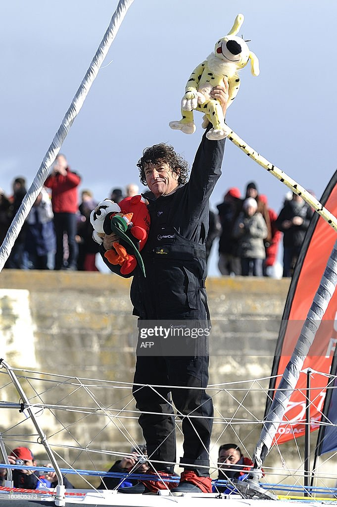 French skipper Jean Le Cam holds stuffed animals as he celebrates on his monohull 'SynerCiel' upon his arrival at the 7th edition of the Vendee Globe solo round-the-world race on February 6, 2013 in Les Sables d'Olonne, western France. Le Cam finished in 5th position after 88 days at sea. AFP PHOTO /JEAN-SEBASTIEN EVRARD