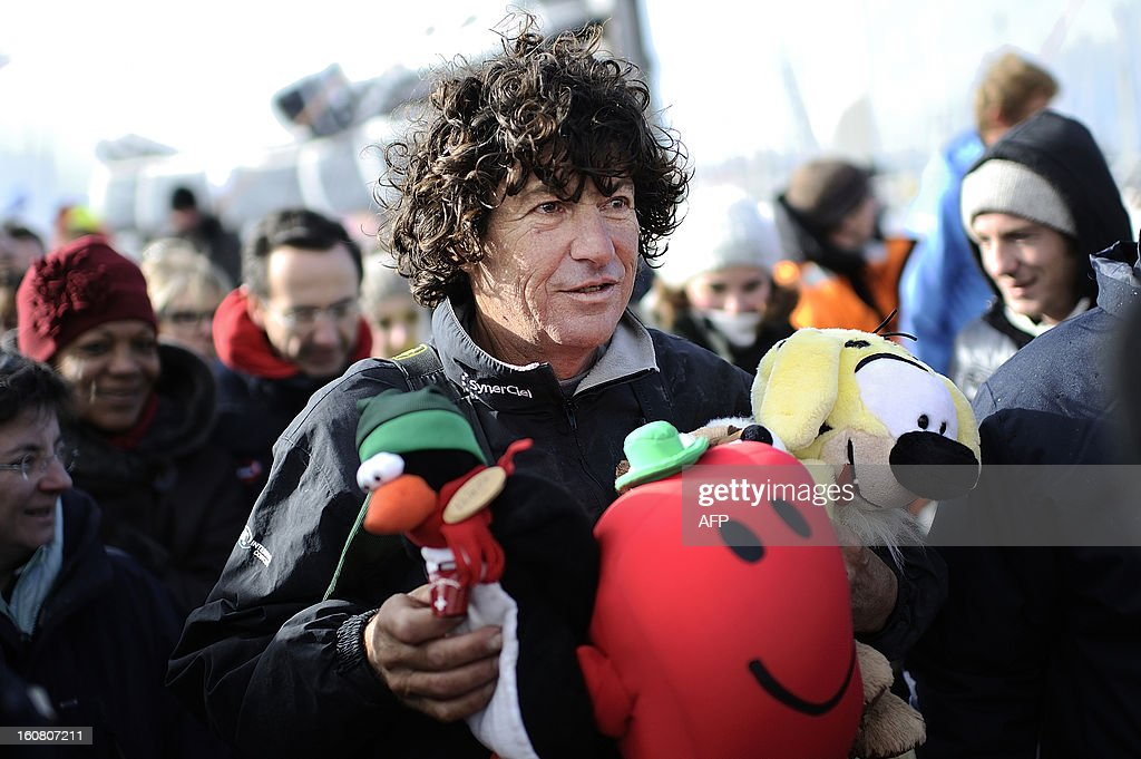 French skipper Jean Le Cam holds stuffed toys as he walks through the crowd after his arrival on his monohull 'SynerCiel' at the 7th edition of the Vendee Globe solo round-the-world race on February 6, 2013 in Les Sables d'Olonne, western France. Le Cam finished in 5th position after 88 days at sea. AFP PHOTO /JEAN-SEBASTIEN EVRARD