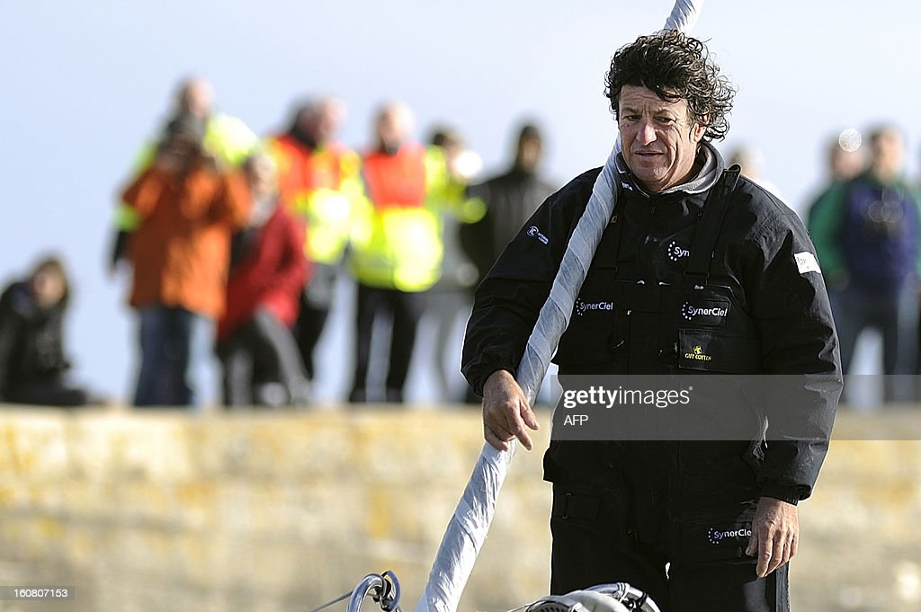 French skipper Jean Le Cam stands on his monohull 'SynerCiel' upon his arrival at the 7th edition of the Vendee Globe solo round-the-world race on February 6, 2013 in Les Sables d'Olonne, western France. Le Cam finished in 5th position after 88 days at sea. AFP PHOTO /JEAN-SEBASTIEN EVRARD