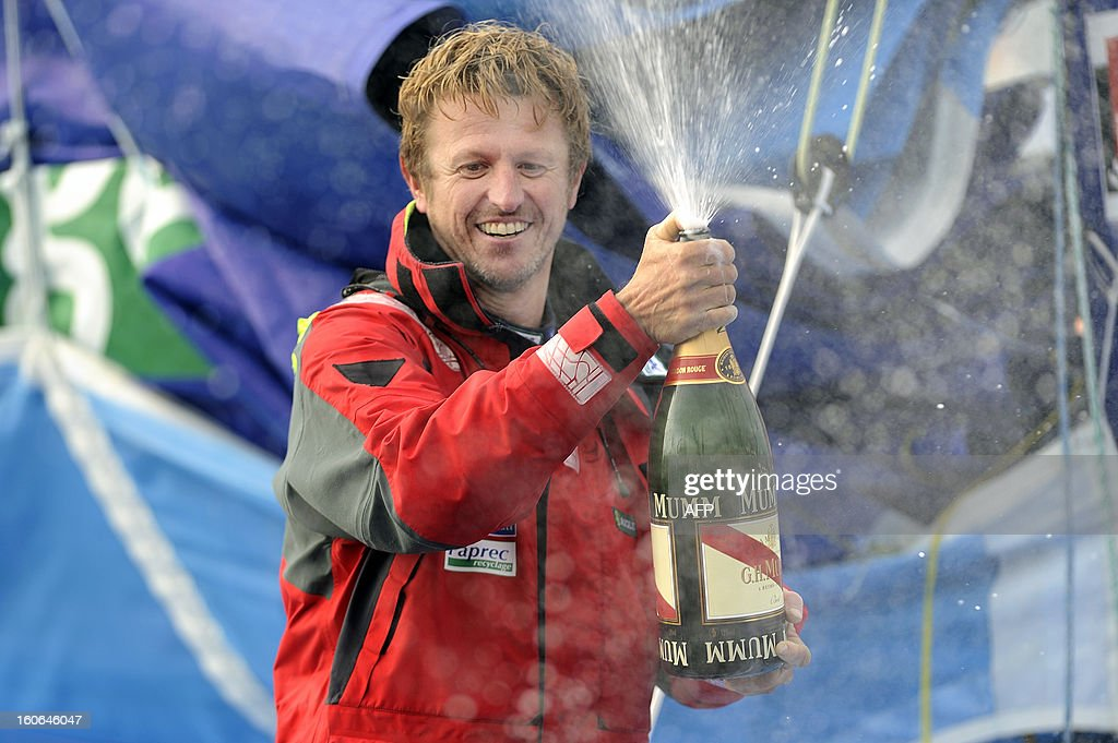 French skipper Jean-Pierre Dick sprays champagne on his monohull 'Virbac Paprec 3' as he finished fourth of the 7th edition of the Vendee Globe solo round-the-world race on February 4, 2013 in Les Sables-d'Olonne, western France. Jean-Pierre Dick was sailing without keel since January 22.