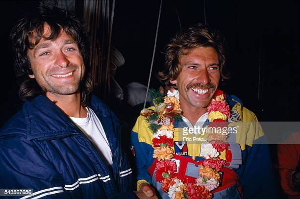 French skipper of Credit Agricole III Philippe Jeantot celebrates with second place competitor Titouan Lamazou skipper of Ecureuil d'Aquitaine after...