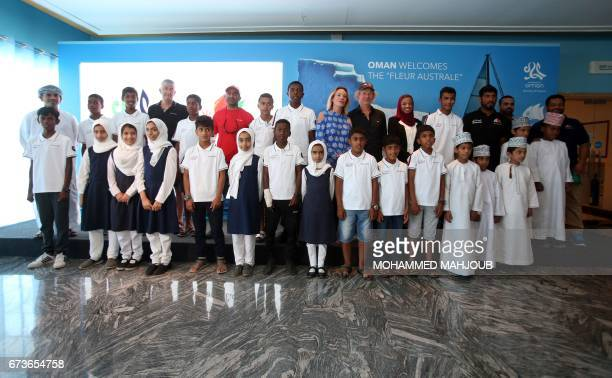 French skipper Philippe Poupon and his wife Geraldine Danon pose for a group picture with Omani children after a press conference in the capital...