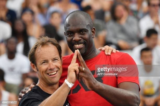 French skipper Thomas Coville and former French taekwondo Olympic champion Pascal Gentil make the 'Eiffel Tower' sign with their fingers a symbol of...