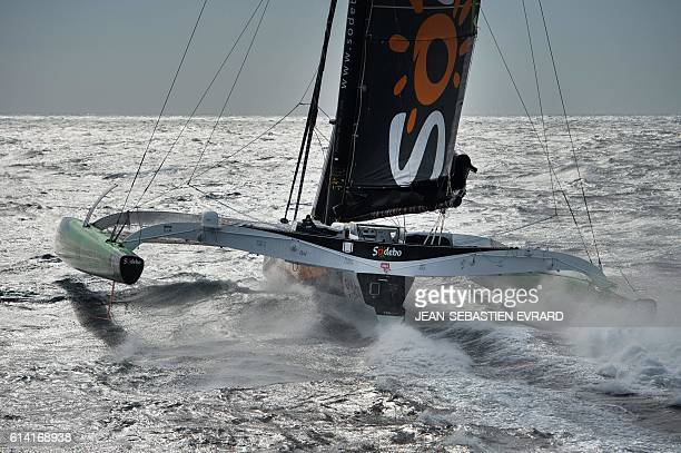 French skipper Thomas Coville navigates aboard his multihull 'Sodebo Ultim' on October 12 2016 off La TrinitesurMer western France Coville prepares...